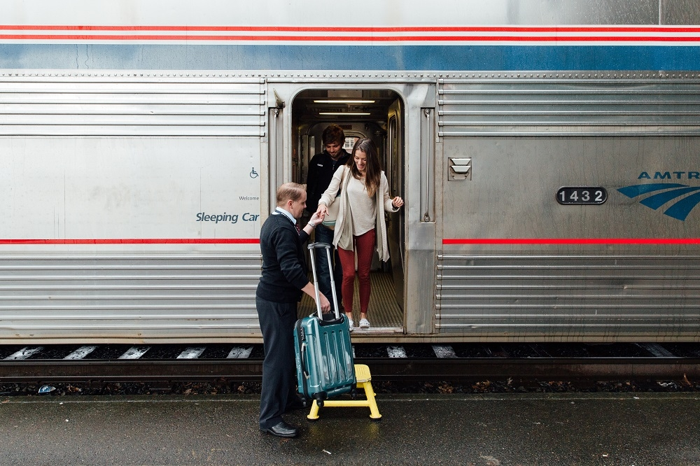 Woman being helped with luggage Amtrak